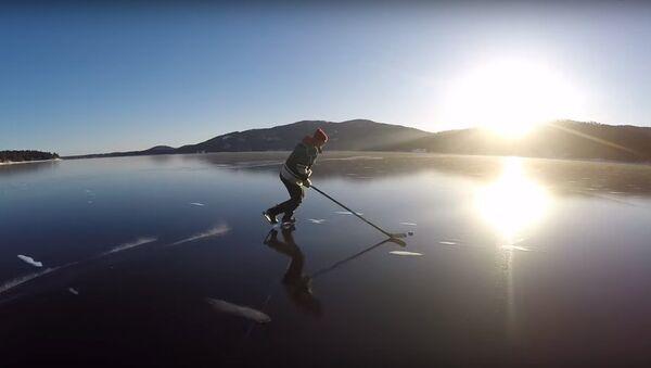 Des hockeyeurs patinent sur la glace cristalline d'un lac - Sputnik France