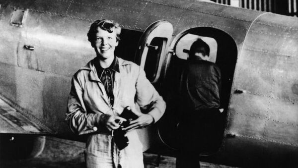 Amelia Earhart standing by her Lockheed Electra with Fred Noonan in the background - Sputnik France