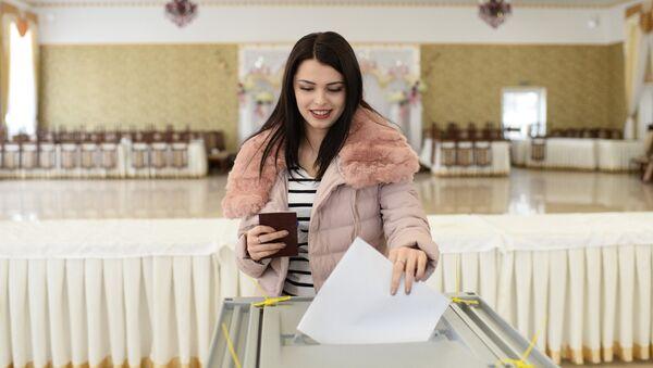 Une jeune femme vote à l'élection présidentielle russe - Sputnik France