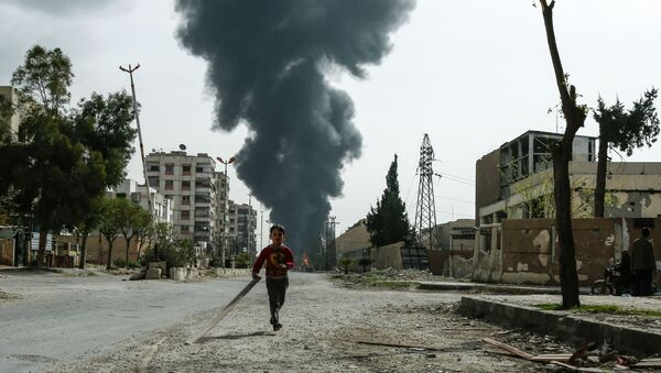A child runs along a street in front of clouds of smoke billowing following a reported air strike on Douma, the main town of Syria's rebel enclave of Eastern Ghouta - Sputnik France