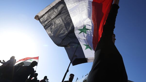 A Syrian government supporter holds up a Syrian national flag as he chants slogans against U.S. President Trump during demonstrations following a wave of U.S., British and French military strikes to punish President Bashar Assad for suspected chemical attack against civilians, in Damascus, Syria, Saturday, April 14, 2018 - Sputnik France