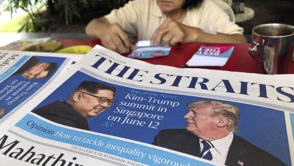 FILE - In this May 11, 2018, file photo, a news vendor counts her money near a stack of newspapers with a photo of U.S. President Donald Trump, right, and North Korea's leader Kim Jong Un on its front page in Singapore. - Sputnik France
