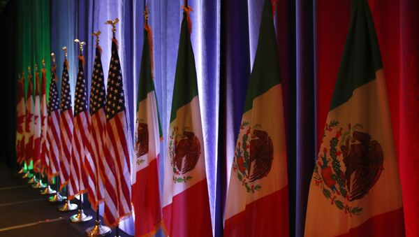 FILE - In this Aug. 16, 2017 file photo, the national flags of Canada, from left, the U.S. and Mexico, are lit by stage lights before a news conference, at the start of North American Free Trade Agreement renegotiations in Washington D.C. Mexico appears to be preparing for the worst as the fourth round of talks open in Washington D.C, Wednesday, Oct. 11, 2017 - Sputnik France
