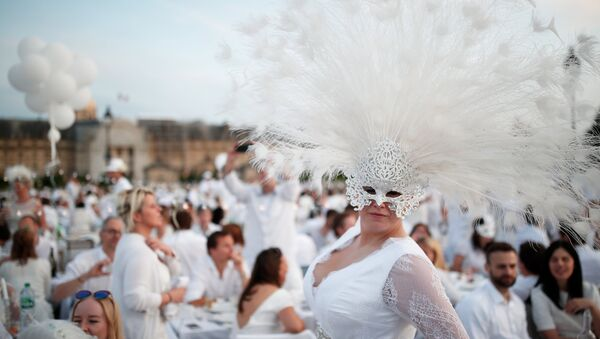 A guest poses near Les Invalides during the Diner en Blanc (Dinner in White) in Paris, France, June 3, 2018. Diners dressed head to toe in white and bringing with them white tablecloths, glassware and other finery, gather for an impromptu open-air dinner, which takes place at a different place in Paris every year. REUTERS/Benoit Tessier - Sputnik France