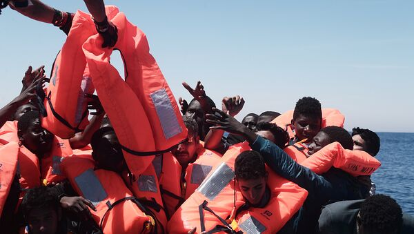 Migrants in an overcrowded plastic raft reach out for life jackets during a search and rescue operation by rescue ship Aquarius, operated by SOS Mediterranean and Doctors without Borders, in central Mediterranean Sea May 18, 2017 - Sputnik France