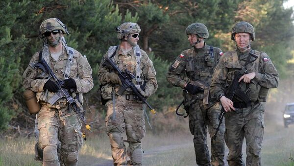 Paratroopers from the U.S. 82nd Airborne Division and the Polish 6th Airborne Division walk together after conducting a a multi-national jump on to a designated drop zone near Torun, Poland, Tuesday, June 7, 2016. The exercise, Swift Response-16, sets the stage in Poland for the multi-national land force training event Anakonda-16. - Sputnik France
