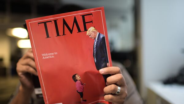 An AFP journalists reads a copy of Time Magazine with a front cover using a combination of pictures showing a crying child taken at the US Border Mexico and a picture of US President Donald Trump looking down, on June 22, 2018 in Washington DC. - Sputnik France