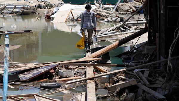 A local resident walks in a flooded area in Mabi town in Kurashiki - Sputnik France