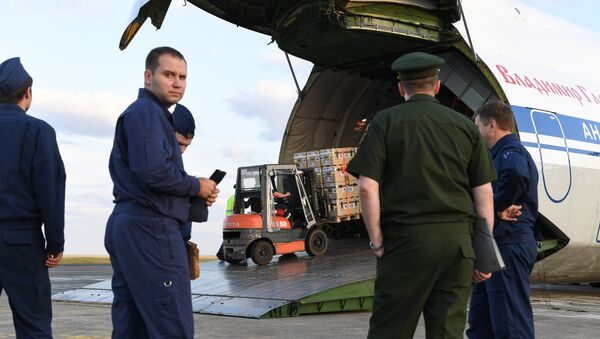 Russian military service personnel watch as supplies are loaded onto an Antonov An-124 Ruslan - Widebody at the former Chateauroux-Deols Marcel Dassault Airport in central France on July 20, 2018. - Sputnik France