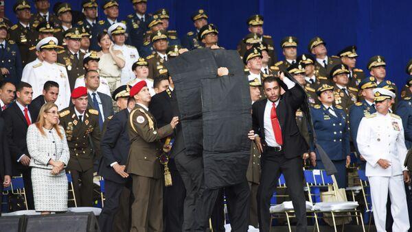 Personal de seguridad rodea al presidente de Venezuela, Nicolás Maduro, durante un incidente mientras daba un discurso en Caracas - Sputnik France