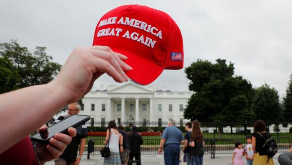 A tourist holds a Make America Great Again hat outside the White House in Washington, U.S., August 2, 2018. - Sputnik France