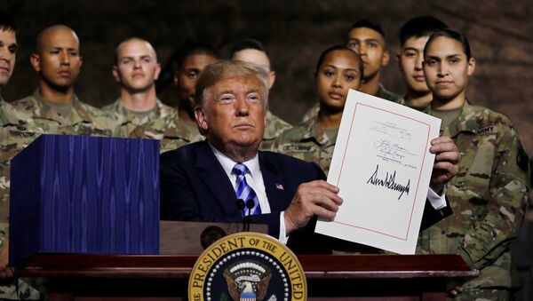 U.S. President Donald Trump holds up the National Defense Authorization Act after signing it in front of soldiers from the U.S. Army's 10th Mountain Division at Fort Drum, New York, U.S., August 13, 2018. REUTERS/Carlos Barria - Sputnik France