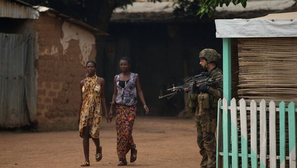 Girls hold hands as they walk past a French soldier holding a position, during an operation to secure part of the Miskine neighborhood, in Bangui, Central African Republic, Thursday, Dec. 26, 2013 - Sputnik France