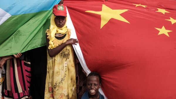 People hold Chinese and Djiboutian national flags as they wait for the arrival of Djibouti's President Ismail Omar Guellehas before the launching ceremony of new 1000-unit housing contruction project in Djibouti, on July 4, 2018. - Sputnik France