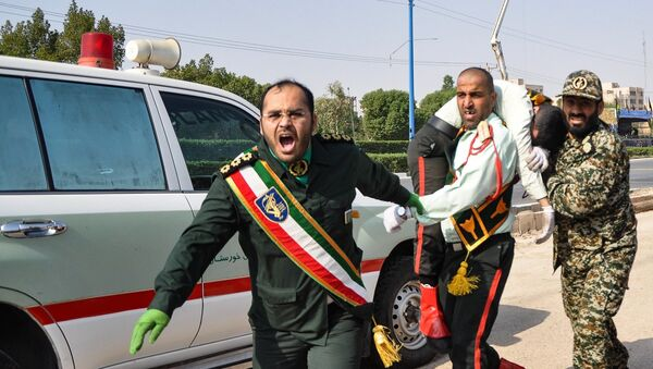 This picture taken on September 22, 2018 in the southwestern Iranian city of Ahvaz shows an Iranian soldier carrying an ijured comrade at the scene of an attack on a military parade that was marking the anniversary of the outbreak of its devastating 1980-1988 war with Saddam Hussein's Iraq. - Sputnik France