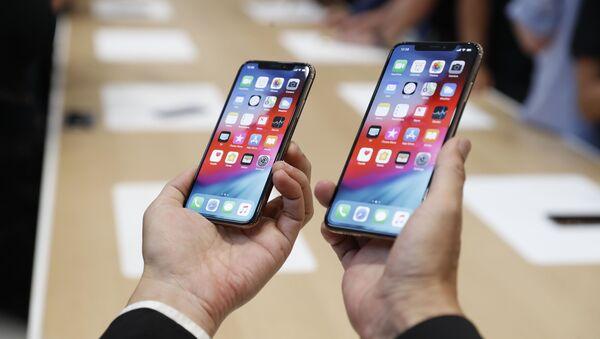 Мужчина держит в руках новые телефоны Apple iPhone XS и XS Max на презентации новых продуктов Apple в американском городе Купертино - Sputnik France