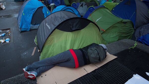 A person sleep next to tents during the evacuation of a makeshift camp on June 16, 2016 in Paris. - Sputnik France