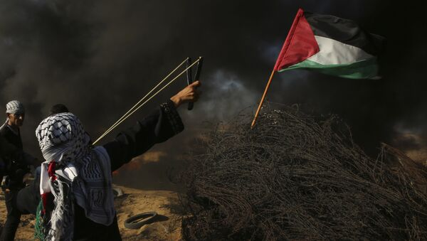 A female protester hurls a stone while others burn tires near the fence of the Gaza Strip border with Israel, during a protest east of Khan Younis, southern Gaza Strip, Friday, Aug. 10, 2018. Violence erupted at the Gaza border Friday after the territory's militant Islamic Hamas rulers and Israel appeared to be honoring a cease-fire that ended two days of intense violence amid efforts by neighboring Egypt to negotiate between the two sides - Sputnik France