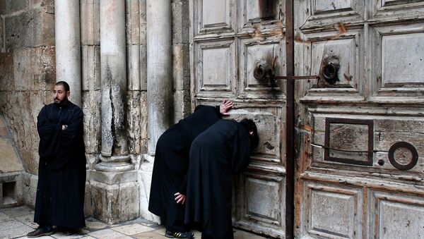 Christian Orthodox priests look through a hole in the main door of the Church of the Holy Sepulchre, before the Holy fire ceremony around Jesus' tomb, in Jerusalem's Old City - Sputnik France
