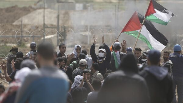 Palestinian protesters chant slogans as they gather during a protest at the Gaza Strip's border with Israel, Friday, April 13, 2018 - Sputnik France