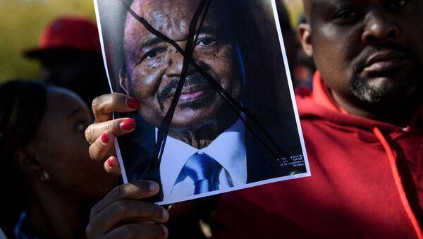 Les gens protestent contre le président camerounais Paul Biya sur l'avenue Pennsylvania, près de la Maison Blanche, le 22 octobre 2018 à Washington, DC. - Sputnik France