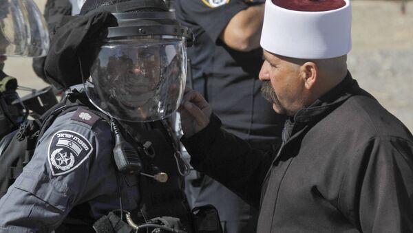 Un membre du communauté druze parle à un membre des forces de sécurité israéliennes lors d'une manifestation contre les élections municipales dans le village de Majdal Chams - Sputnik France