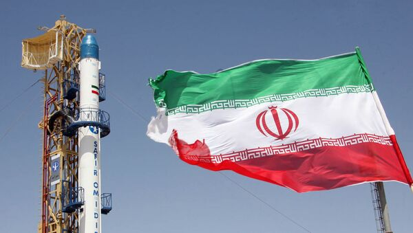 Un drapeau iranien flottant devant la fusée iranienne Safir Omid - Sputnik France