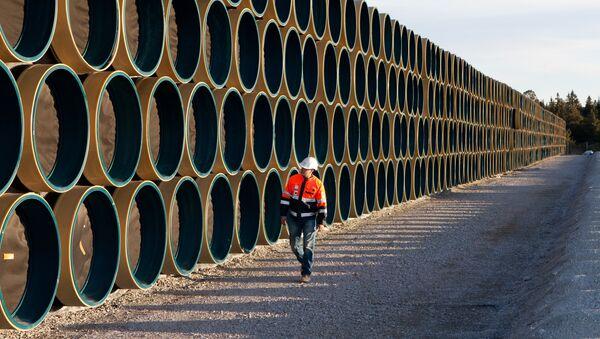 Ein Bauarbeiter vor den Metallröhren für die Gaspipeline Nord Stream 2 (Archivbild) - Sputnik France