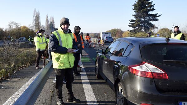 A demonstrator of the Yellow Vests movement (Gilets Jaunes) distributes tracts to a car driver on November 18, 2018 at the border point with Belgium in Crespin near Valenciennes, northern France, a day after a nationwide protest against high fuel prices. - Sputnik France