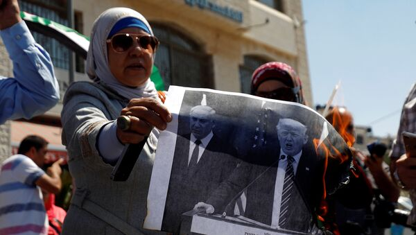 A Palestinian woman burns a picture of U.S. President Donald Trump and Israeli Prime Minister Benjamin Netanyahu during a protest against a U.S. decision to cut funding to the United Nations Relief and Works Agency (UNRWA), in Ramallah, in the occupied West Bank September 4, 2018.  - Sputnik France