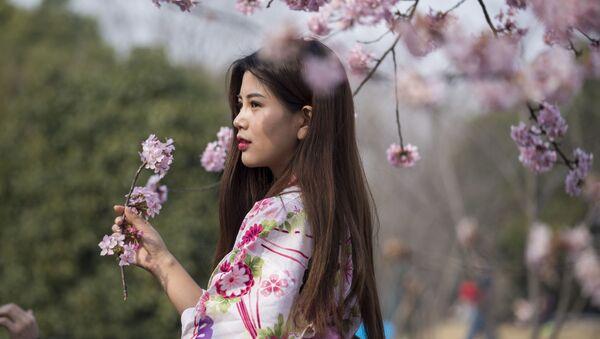 Девушка с веткой цветущей сакуры в Шанхае - Sputnik France