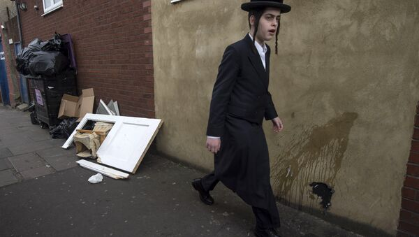 An Orthodox jew walks past a damaged door belonging to the Ahavas Torah synagogue in the Stamford Hill area of north London on March 22, 2015 - Sputnik France