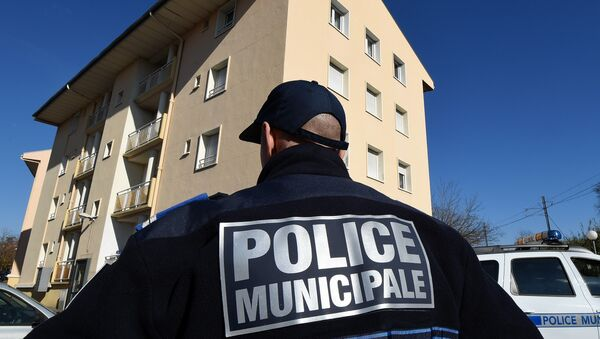 A municipal police officer stands January 22, 2015 in front of a building in Beziers, southern France, where a Russian Chechen suspected of preparing a terrorist attack was living before his January 19 arrest - Sputnik France