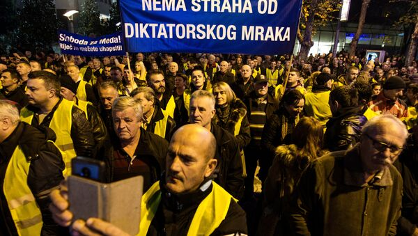 Protesters wearing yellow vests hold a banner during a protest against the arrest of Nebojsa Medojevic in Podgorica - Sputnik France