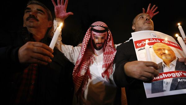 An activist, wearing a mask depicting Saudi Crown Prince Mohammed bin Salman, holds up his hands, painted with fake blood as he protests the killing of Saudi journalist Jamal Khashoggi, during a candlelight vigil outside Saudi Arabia's consulate in Istanbul, Thursday, Oct. 25, 2018 - Sputnik France