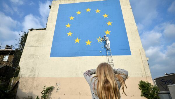 A young girl looks at artwork attributed to street artist Banksy, depicting a workman chipping away at one of the 12 stars on the European Union, seen on a wall in the ferry port of Dover, Britain, May 7, 2017. - Sputnik France