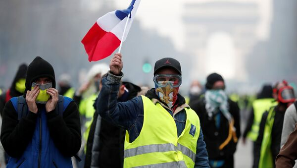Masked protesters wearing yellow vests, a symbol of a French drivers' protest against higher fuel prices, take part in a demonstration on the Champs-Elysees in Paris, France, November 24, 2018 - Sputnik France