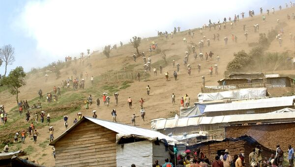 People carry bags of cassiterite (tin ore), coltan, which is used in mobile telephones and computers, and manganese down a hill from the Mudere mine, near Rubaya, some 9 kms from the eastern Democratic Republic of Congo city of Goma (File) - Sputnik France