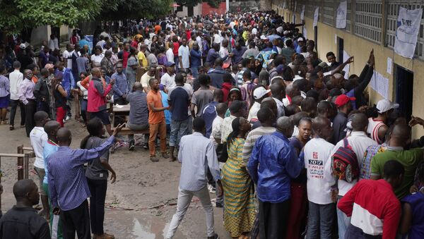 Hundreds of Congolese voters who have been waiting at the St. Raphael school in the Limete district of Kinshasa Sunday Dec. 30, 2018, storm the polling stations after the voters listings were finally posted five hours after the official start of voting. Forty million voters are registered for a presidential race plagued by years of delay and persistent rumors of lack of preparation. (AP Photo/Jerome Delay) - Sputnik France