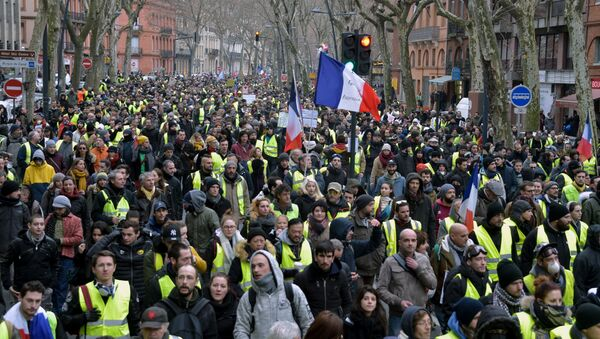 Protestors wearing Yellow Vests (gilets jaunes) hold French flags as they take part in an anti-government demonstration called by the Yellow Vest movement on January 12, 2019, - Sputnik France