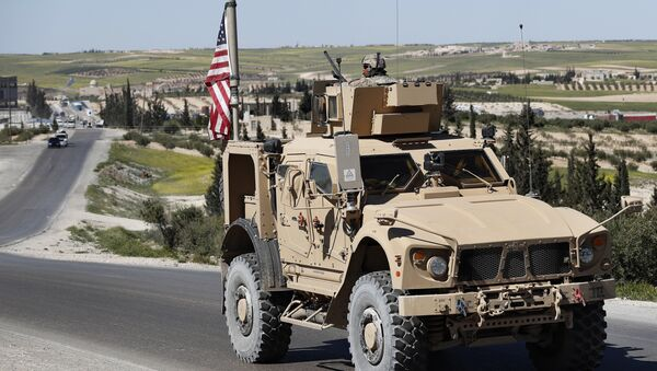 A U.S. soldier sits on an armored vehicle on a road leading to the tense front line with Turkish-backed fighters, in Manbij, north Syria, Wednesday, April 4, 2018 - Sputnik France