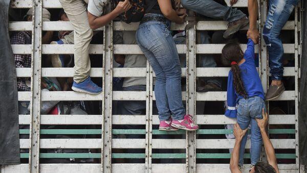 Венесуэльские мигранты лезут в грузовик на дороге из Кукуты в Памплону, Колумбия - Sputnik France