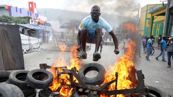 Протестующий перепрыгивает через горящую баррикаду во время акции протеста против правительства на улицах Порт-о-Пренса, Гаити - Sputnik France