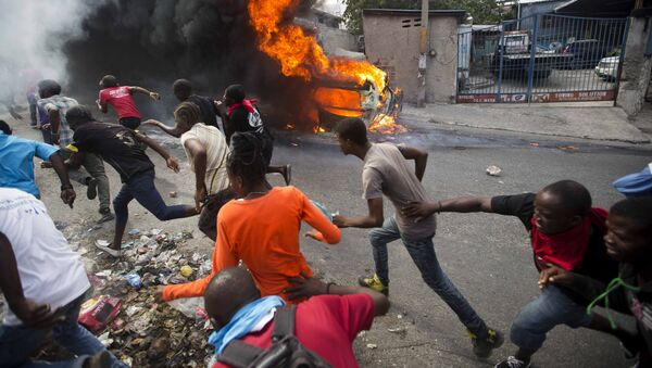 Demonstrators run away from police who are shooting in their direction, as a car burns during a protest demanding the resignation of Haitian President Jovenel Moise in Port-au-Prince, Haiti, Tuesday, Feb. 12, 2019. - Sputnik France