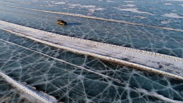 A car drives along a road connecting the banks of the ice-covered Yenisei River south of Krasnoyarsk - Sputnik France