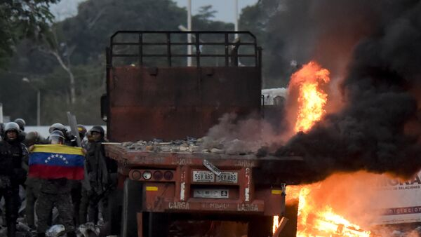 Venezuelan security forces display a national flag next to a truck which was burnt during the weekend when trying to enter the country with humanitarian aid, during clashes with supporters of Venezuelan opposition leader Juan Guaido on the Venezuelan side of the Francisco de Paula Santander International Bridge, as seen from Cucuta, Colombia, on February 25, 2019. - Sputnik France