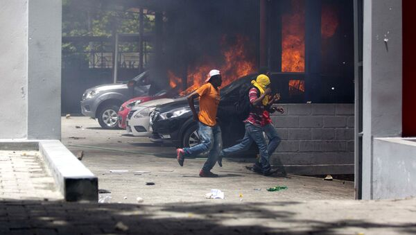 People run away after cars were set on fire at a Nissan dealership during protests over a fuel price increase in Port-au-Prince, Haiti, on Saturday, July 7, 2018 - Sputnik France