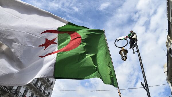 This picture taken on March 22, 2019 shows an Algerian national flag flying during a demonstration against ailing President Abdelaziz Bouteflika in the capital Algiers. - Sputnik France