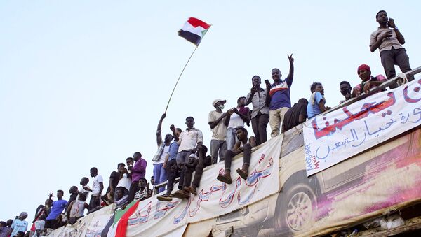 Demonstrators wave their national flag as they attend a protest rally demanding Sudanese President Omar Al-Bashir to step down outside Defence Ministry in Khartoum, Sudan April 10, 2019. - Sputnik France