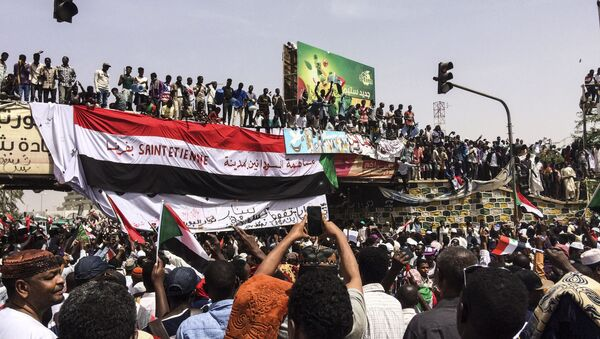Demonstrators gather in Sudan's capital of Khartoum, Friday, April 12, 2019. The Sudanese protest movement has rejected the military's declaration that it has no ambitions to hold the reins of power for long after ousting the president of 30 years, Omar al-Bashir. The writing on the Sudanese flag says 'With the participation of the Sudanese in Saint Etienne, France.' - Sputnik France